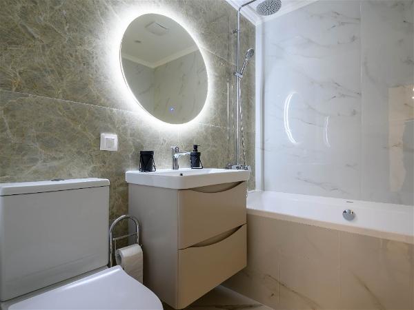 banheiro com espelho redondo com led atrás