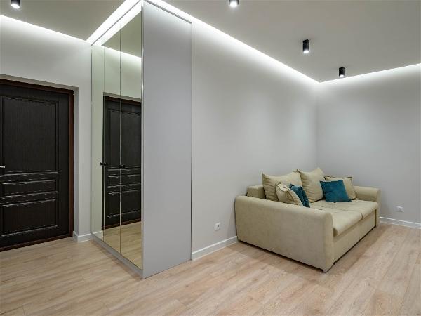sala de estar com sofá claro à direita com led embutido no teto