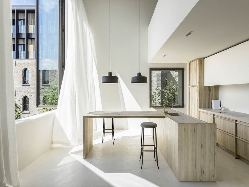 cozinha minimalista com luz natural entrando por janela grande aberta